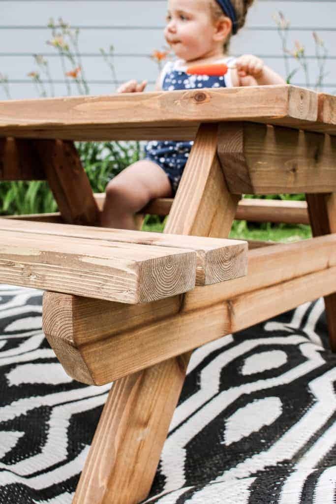 shows toddler eating a Popsicle on a wooden kids picnic table on top of a black and white boho outdoor rug