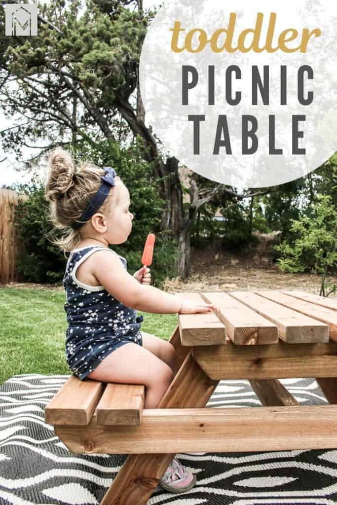 shows a side view of the toddler eating a Popsicle wearing a navy blue outfit on a wood picnic table on a boho black and white rug with overlay text that says toddler picnic table