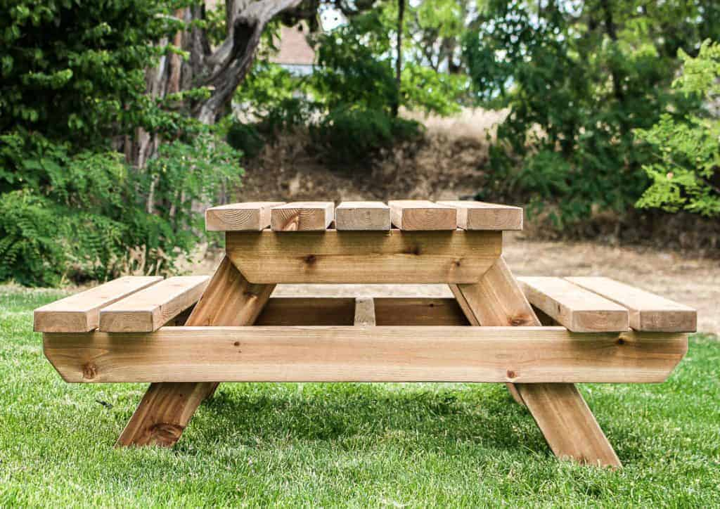 shows a front view of the wood toddler sized picnic table in a backyard on grass