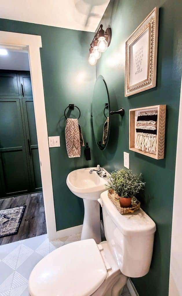 shows a view from the shows of the toilet and sink with a dark green walls and gray tile floors with white stripes and boho home decor