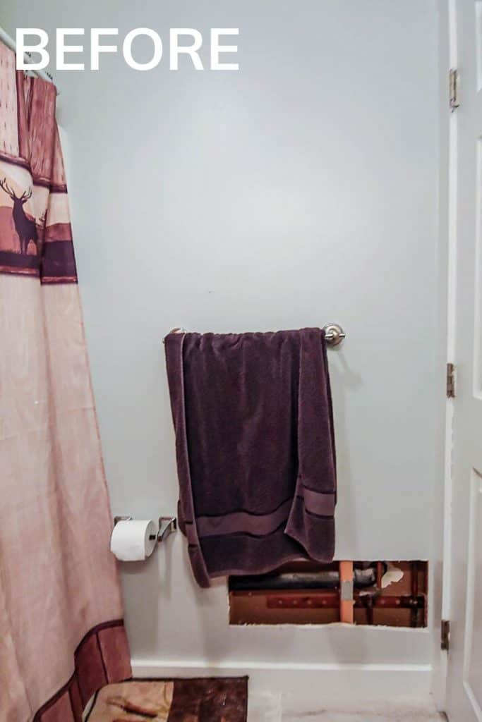 shows a wall with a purple towel and and toilet paper holder with a hole in the drywall on the bottom right with a shower curtain and rug with overlay text that says before