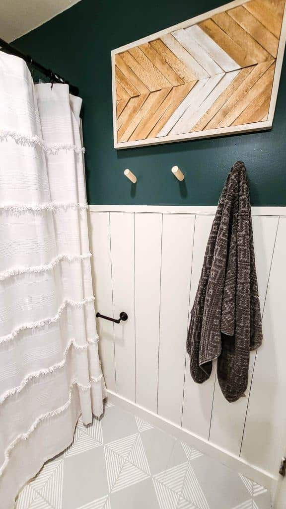 shows a corner of small boho style bathroom with the vertical shiplap wall and dark green wall with a wood wall towel hook and wood framed decor next to a white shower curtain  with gray tile floors with white stripes