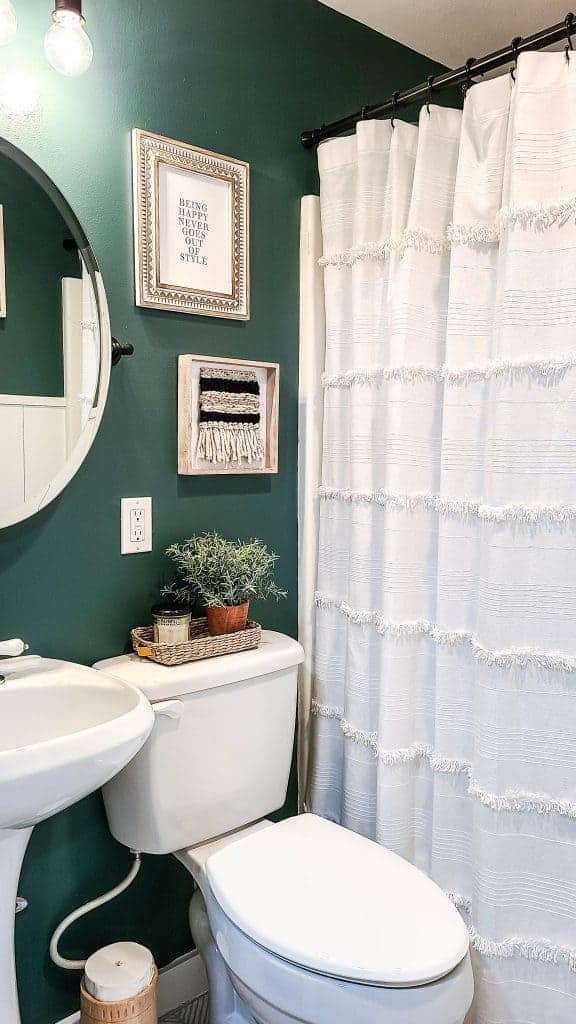 shows a dark green painted bathroom with white toilet, shower curtain, and sink with boho home decor on walls and top of toilet