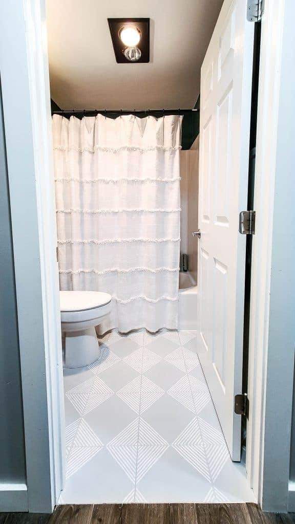 shows a white shower curtain in a small boho styled bathroom with a white toilet and gray painted tile floors with white stripes