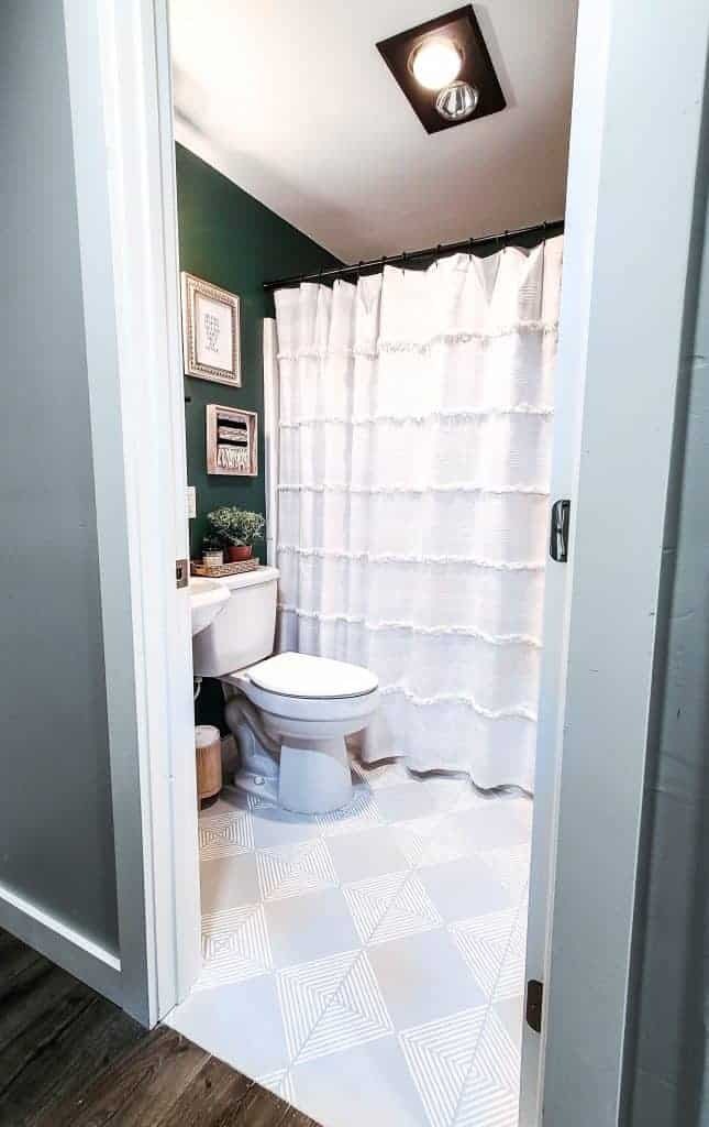 shows a dark green painted small bathroom with white toilet and shower curtain, and small stand alone sink with gray with white stripes tile floor and boho wall decor
