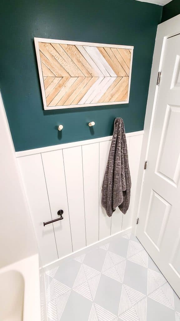 shows a vertical shiplap wall with a dark green wall with a bohos tyle wood frame with arrow made with wood shims and gray tile floors with white stripes