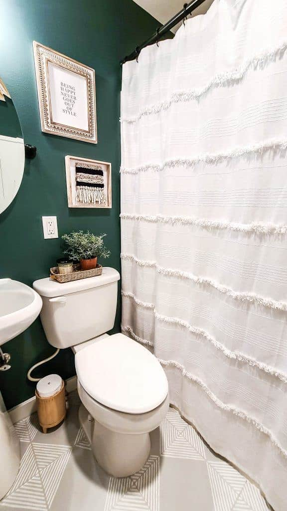 shows a corner of the bathroom with a toilet and white sink next to a white shower curtain with a dark green walls and gray tile floors with white stripes