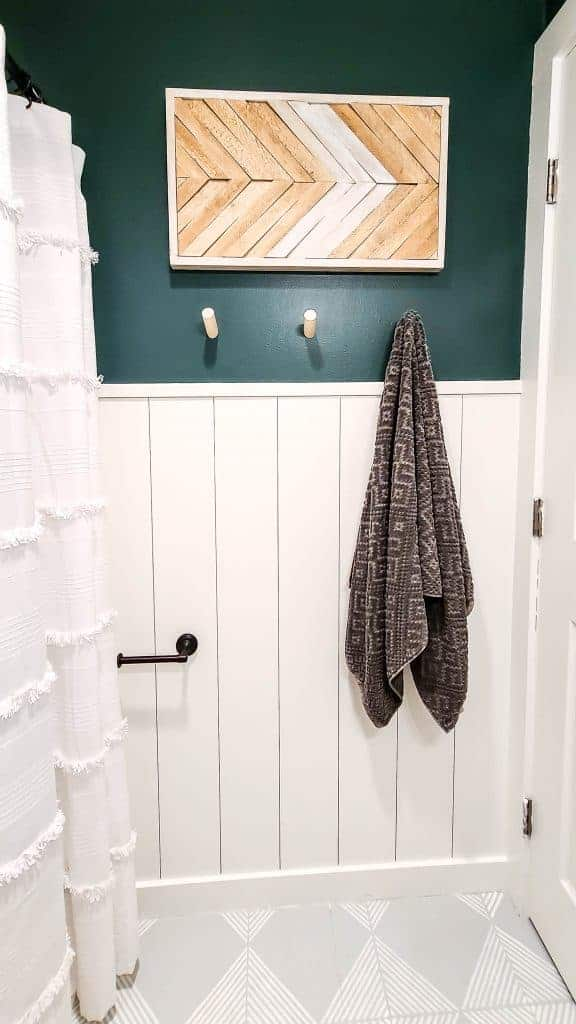 shows a picture of a dark green painted walls in small bathroom with no windows with the bottom half having white shiplap installed vertically and a wood frame and modern wooden towel hooks with gray tiled floors with white stripes