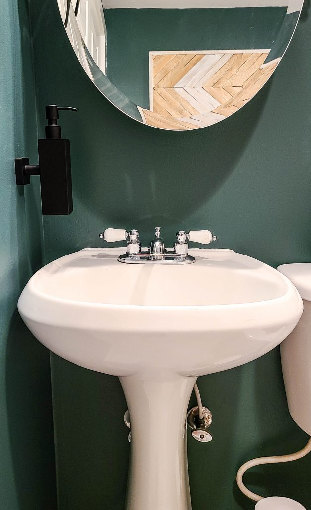 white sink with the bottom of a oval mirror and dark green wall with a black wall mounted soap dispenser