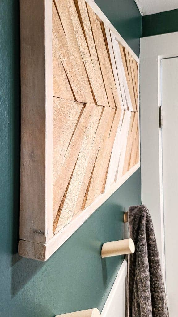 shows a modern wood frame made with wood shims on a dark green wall with wood towel hooks below
