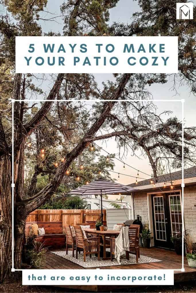 Cozy outdoor dining space on wooden deck in backyard with string lights, outdoor rug, wood table and chairs and umbrella with trees overhead with text overlay that says 5 ways to make your patio cozy that are easy to incorporate
