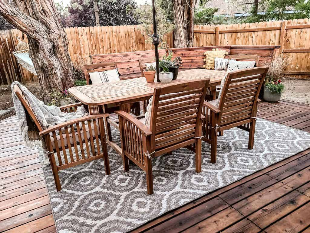 Acacia wood dining set with 6 chairs with tan cushions, boho throw pillows and potted succulents in the middle of the table with a gray patterned outdoor rug underneath table, and wood fence in the background