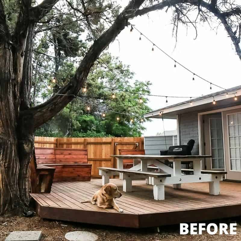 shows a back yard with a wood patio with a bench and white table with a dog on it