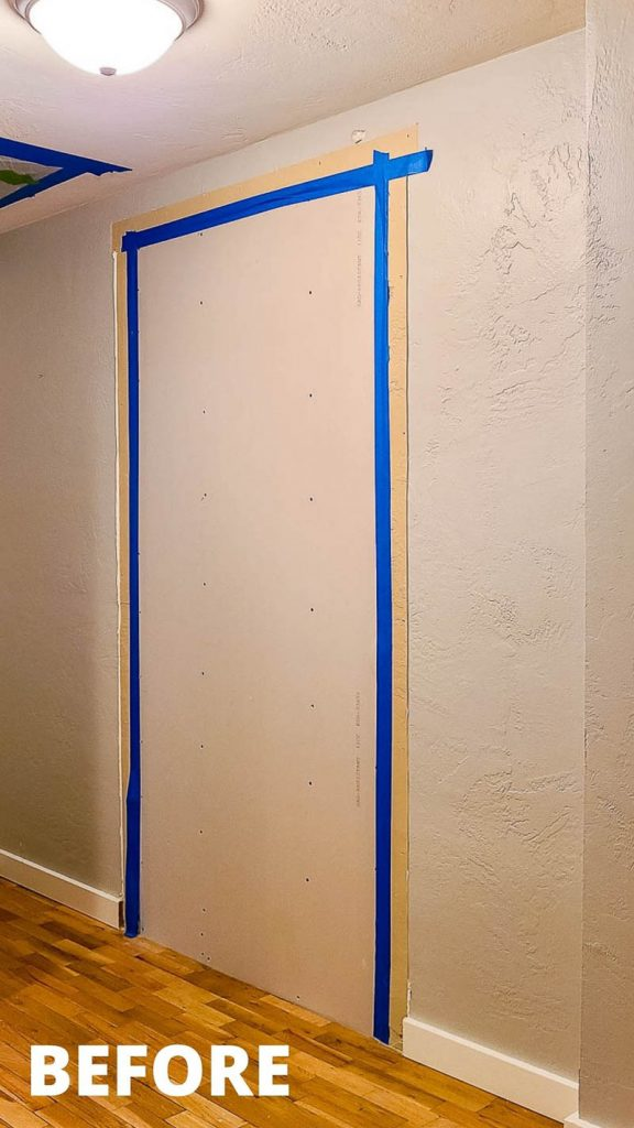 shows a hallway with a dry wall covering a doorway with blue tape