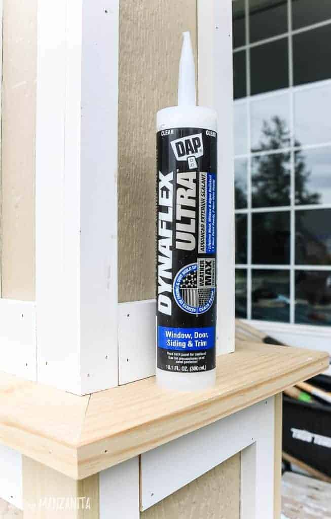 shows a tube of dynaflex ultra exterior caulk sitting on a post outside a house