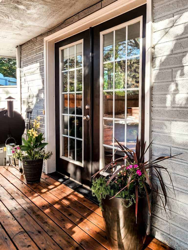 Freshly painted black french doors leading to wood deck with blue brick house and potted plants on both sides of the door