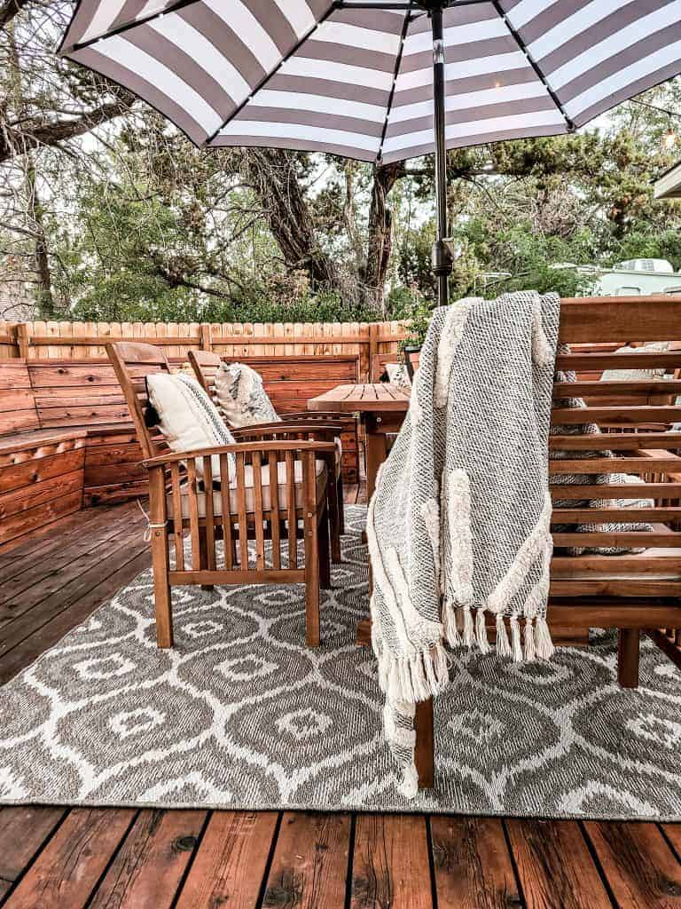 Zoomed in view of outdoor dining table with chairs with throw pillows in each chair and blanket draped over the back of one of the chairs to some extra cozy texture