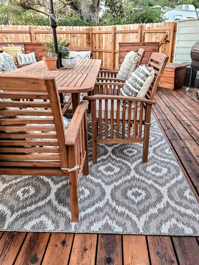 Close up view of wood table and chairs in backyard on wood deck with a gray boho patterned outdoor rug underneath with outdoor throw pillows on the chairs and small potted succulents on table with wood fence in background