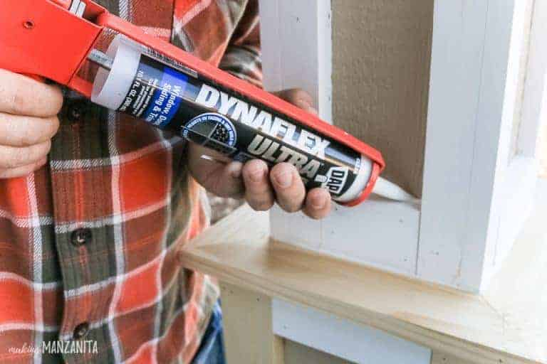 shows a man using the tube of caulk on a post outside