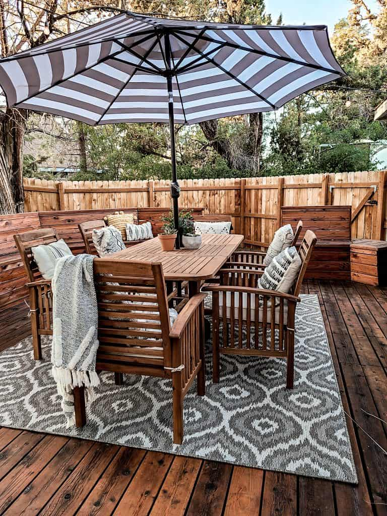 Mohawk Home Oasis Morro Large gray rug with a boho pattern under acacia wood table with chairs on deck with black and white striped umbrella