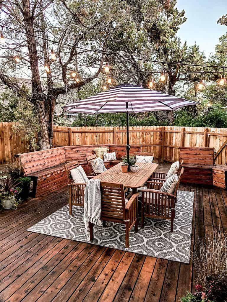 Glamorous wood deck with wood dining set, boho pattern outdoor rug, string lights and juniper trees in the background