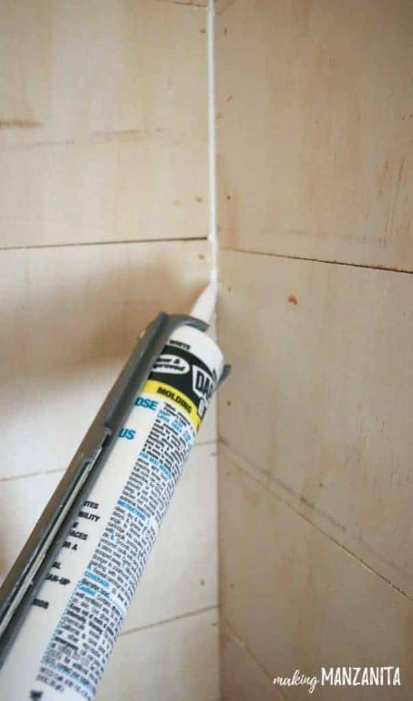 shows a tube of caulk being squeezed into the corner of plywood shiplap on wall