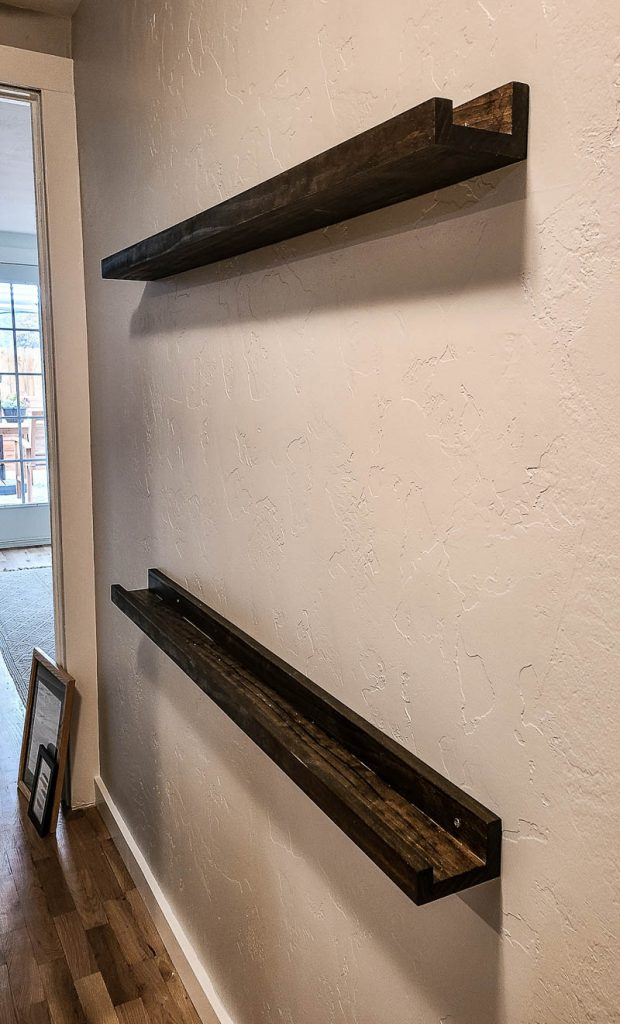 shows dark stained picture ledge shelves on a gray wall in a hallway