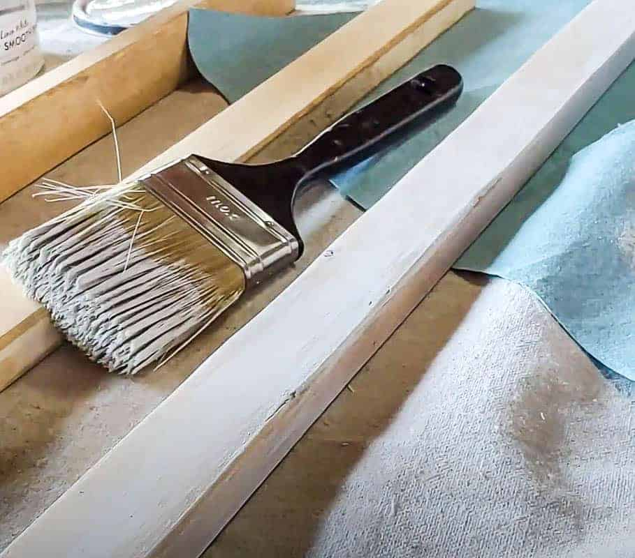 shows piece of wood laying down on a blanket with a paint brush
