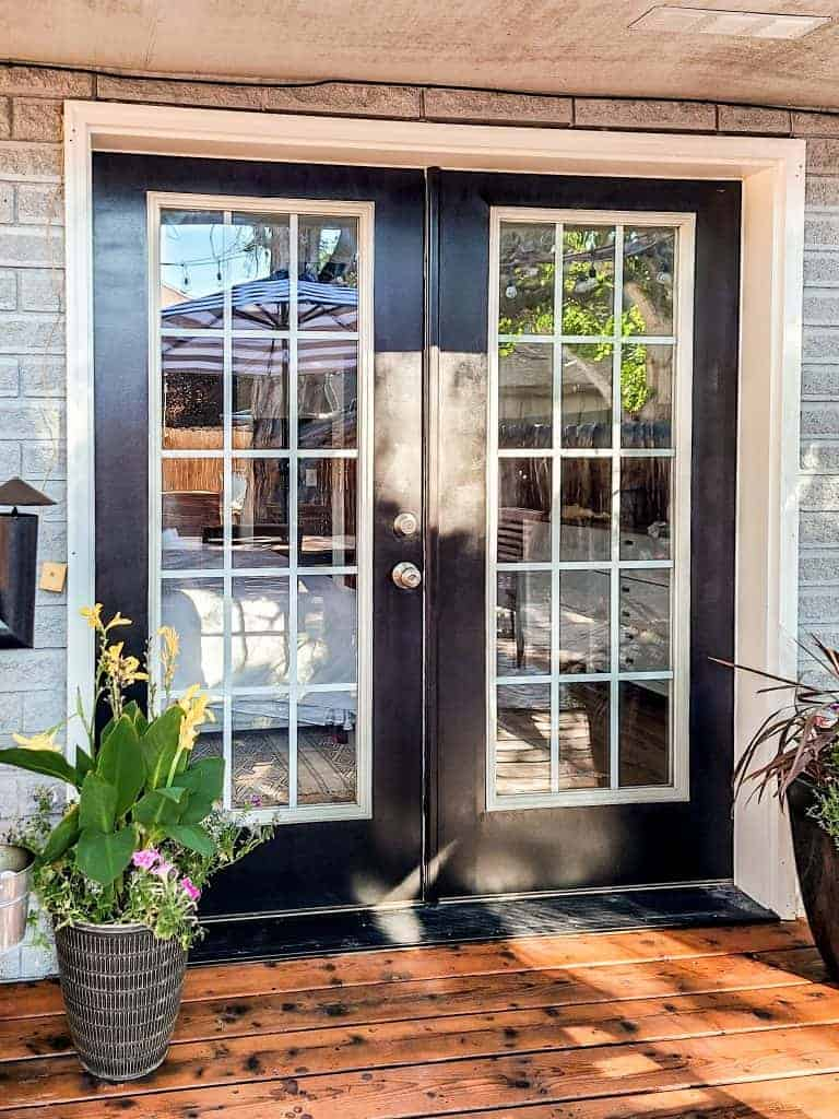 French doors leading to wood deck painted black on the exterior with gray blue house and potted plants on the ground on either side of the doors.