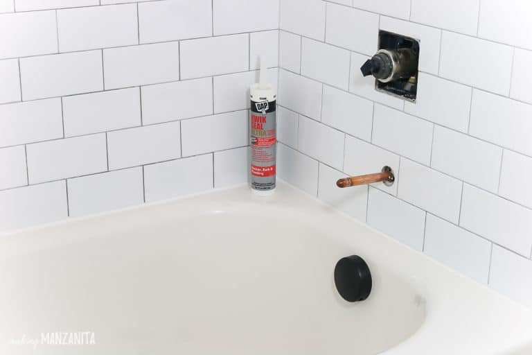 shows a tube of caulk sitting on the corner ledge of a white bathroom tub with subway tile on walls