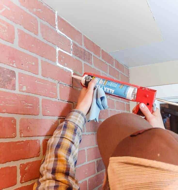 shows a man caulking the cracks between faux brick panels hung on wall