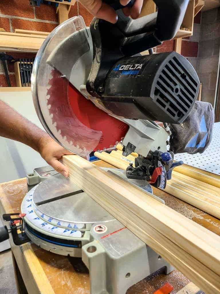 shows a Delta miter saw cutting into a stack of wood boards