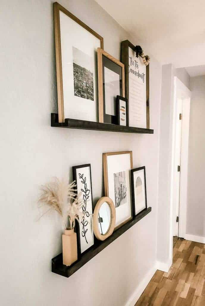 shows the wood ledge shelves with multiple wood frames on  gray wall in a hallway