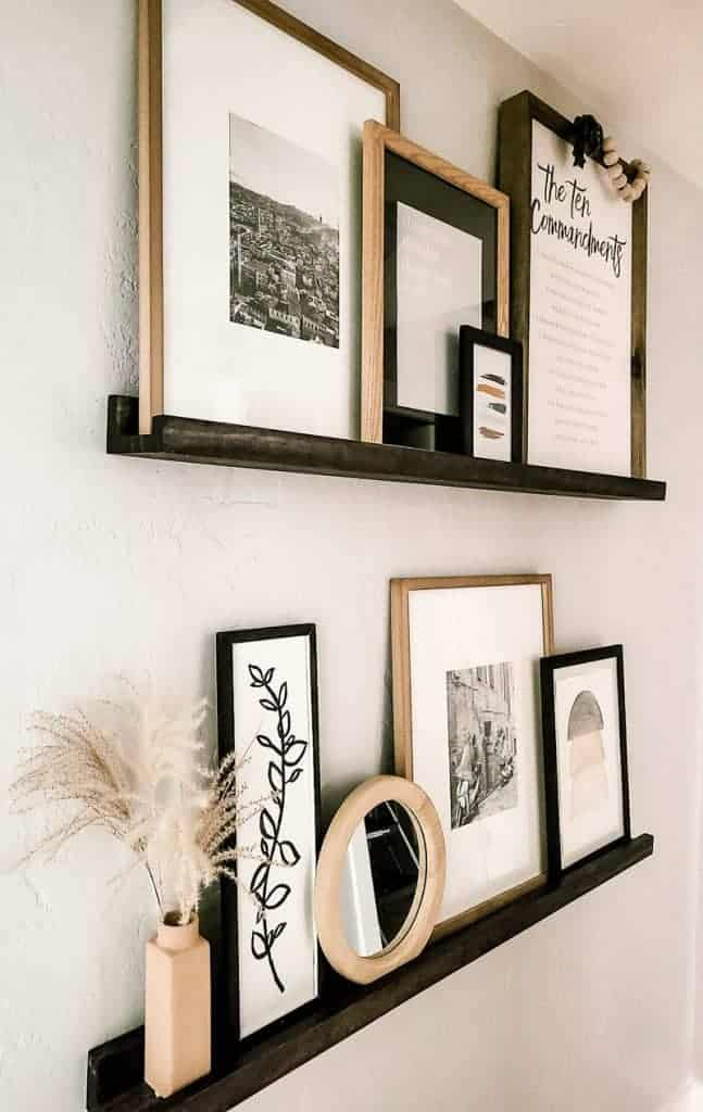 shows another angle of the dark stained ledge shelves with upcycle frames on a gray wall in a hallway