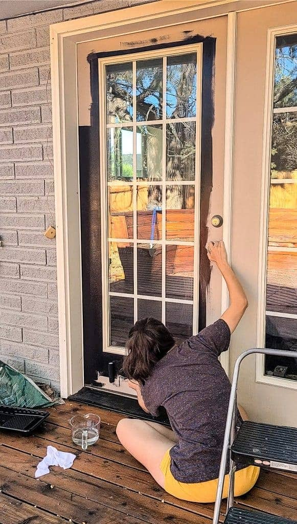 shows a woman painting the french doors black