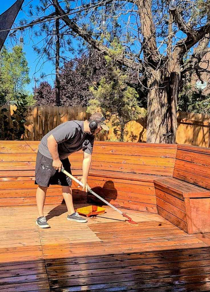 shows a man staining the wood of a backyard patio