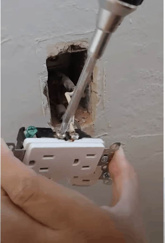shows a screw driver unscrewing the outlet from the wires