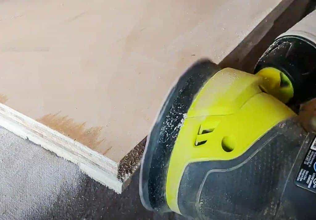 shows an orbital sander sanding the sides of plywood on the DIY wood wall art