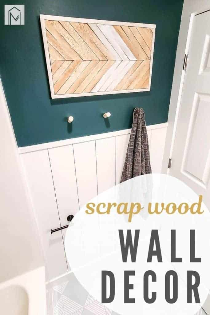 Boho wall decor with wood shim arrow pattern on wall in bathroom above towel rack with text overlay that says scrap wood wall decor