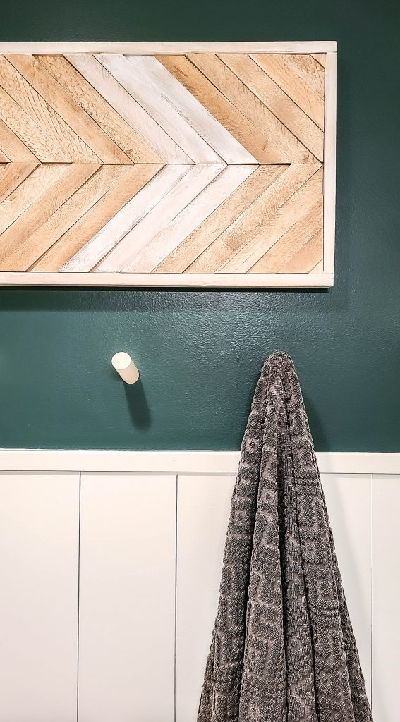 wooden wall art piece on a dark teal wall with shiplap walls and wood dowels underneath it with a towel