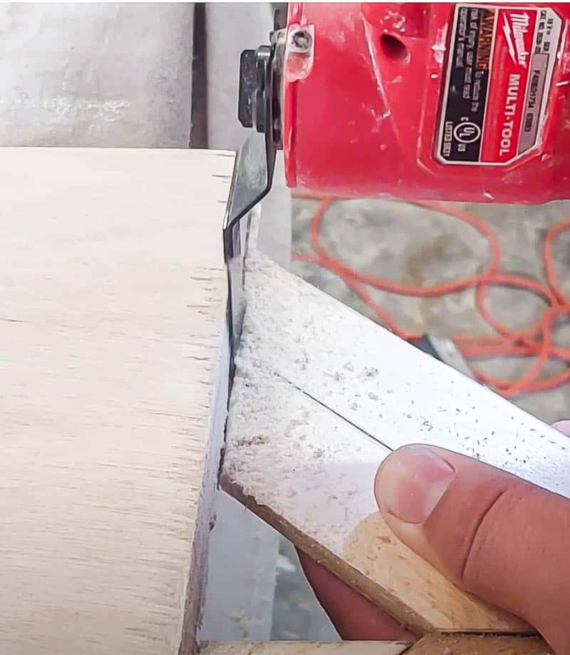 shows a multi-tool trimming the edges of the wood shims overhang along the edge of the plywood on DIY wood wall decor piece