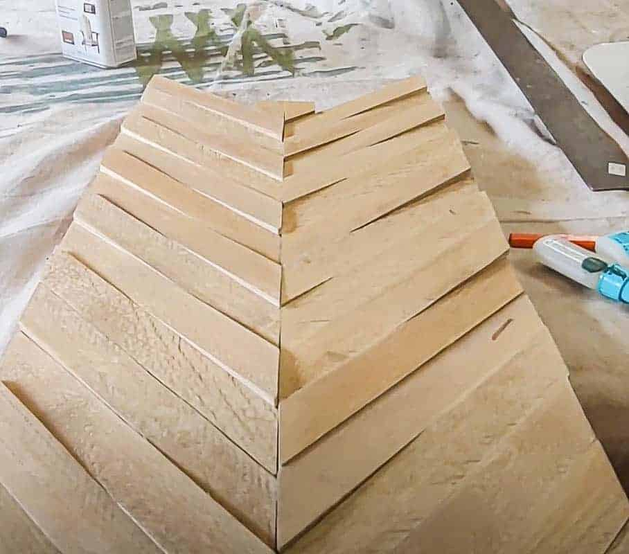 shows pieces of diagonal wood creating an arrow on the plywood
