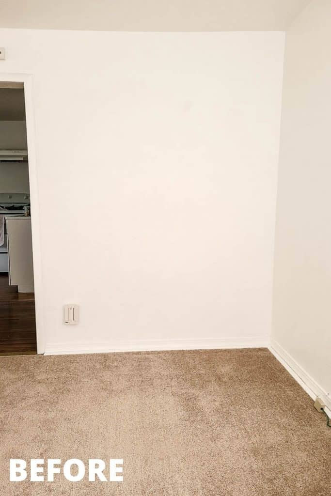 shows a empty white corner in a studio apartment with before in the corner of the picture