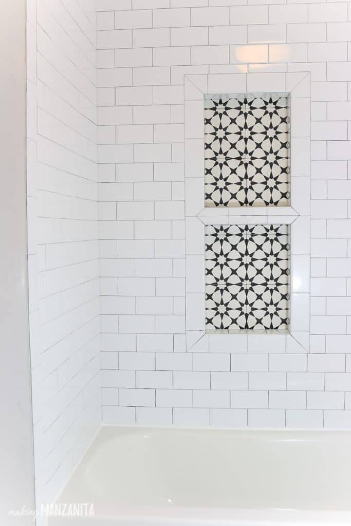 shows white rectangular subway tile and black and white cement tile pattern in a shower niche