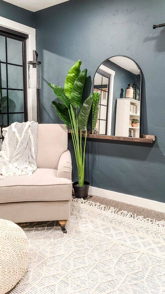 arched mirror with black frame on a dark wood shelf ledge next to a faux tropical plant, boho textured area rug with tassels, and white linen chair with dark teal walls