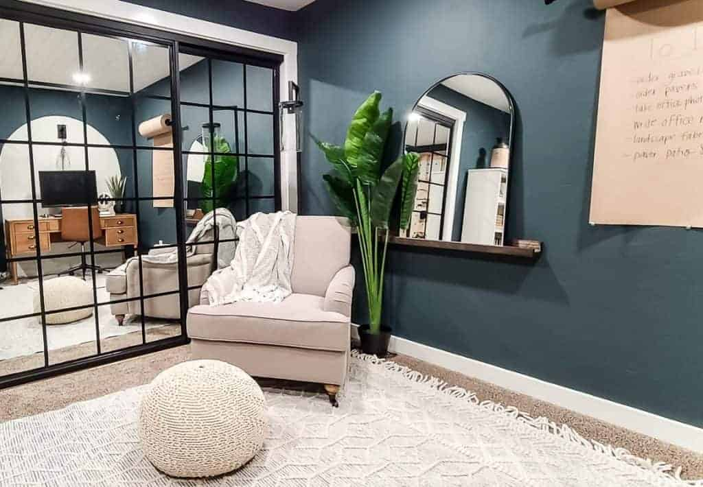 shows the corner of the dark teal office with a white arm chair, arch mirror on ledge shelf, plant with white boho rug, closet doors with mirror