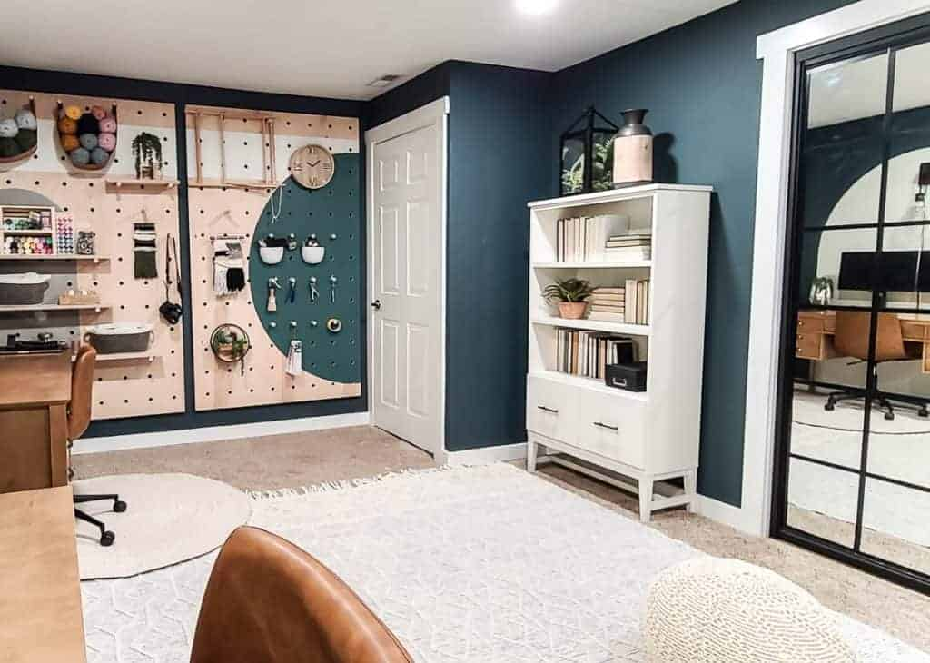 shows the other corner of the office with dark green walls, white book case with filing drawers and a giant wood pegboard to hold craft and art supplies