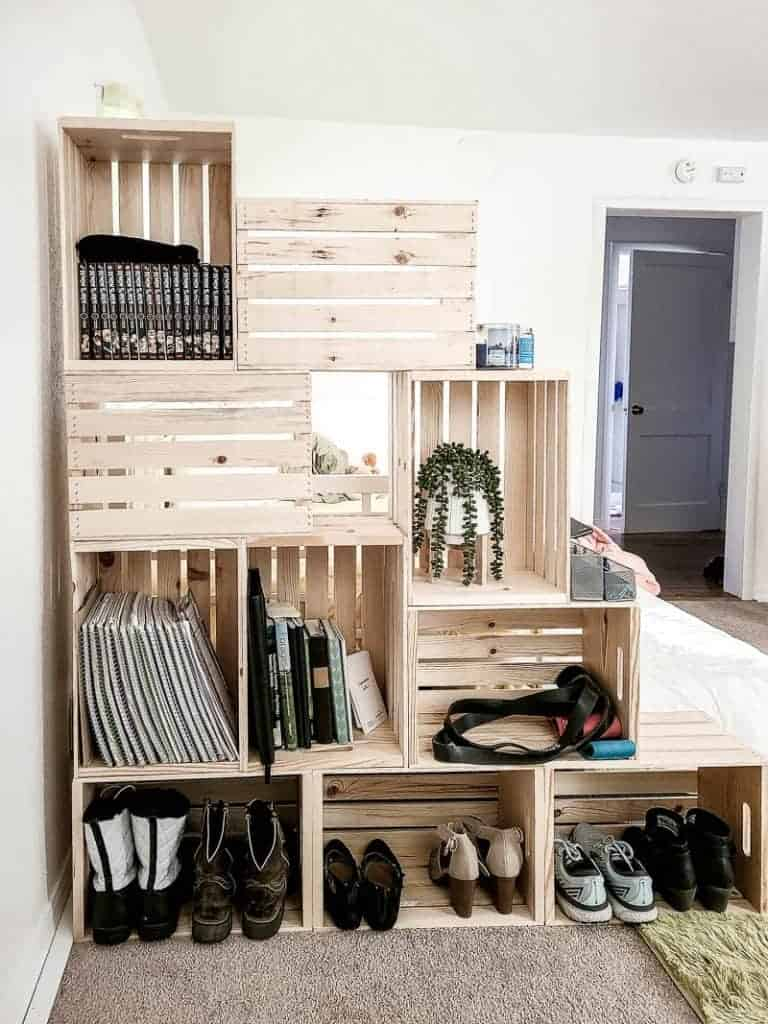 shows the 10 wood crates filled with shoes, books and plants in a white room