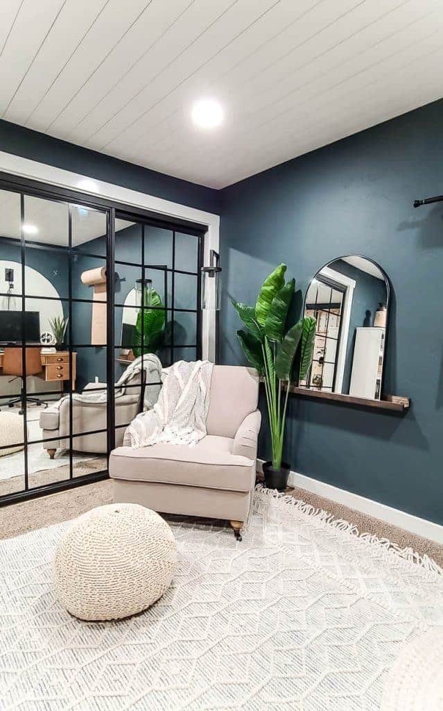 shows a mirror with rounded top and black frame on a dark wood shelf ledge next to a plant and white chair and macrame floor poof foot rest with dark teal walls with mirrored closet doors in background and white shiplap on ceiling