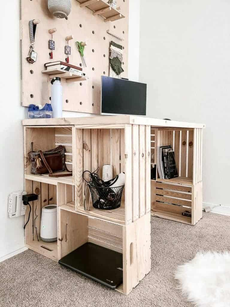 shows angled view of DIY wood crate desk with a computer and wood pegboard wall above it